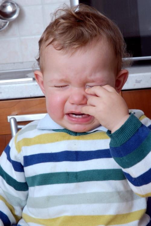 Niño llorando en una cocina.
